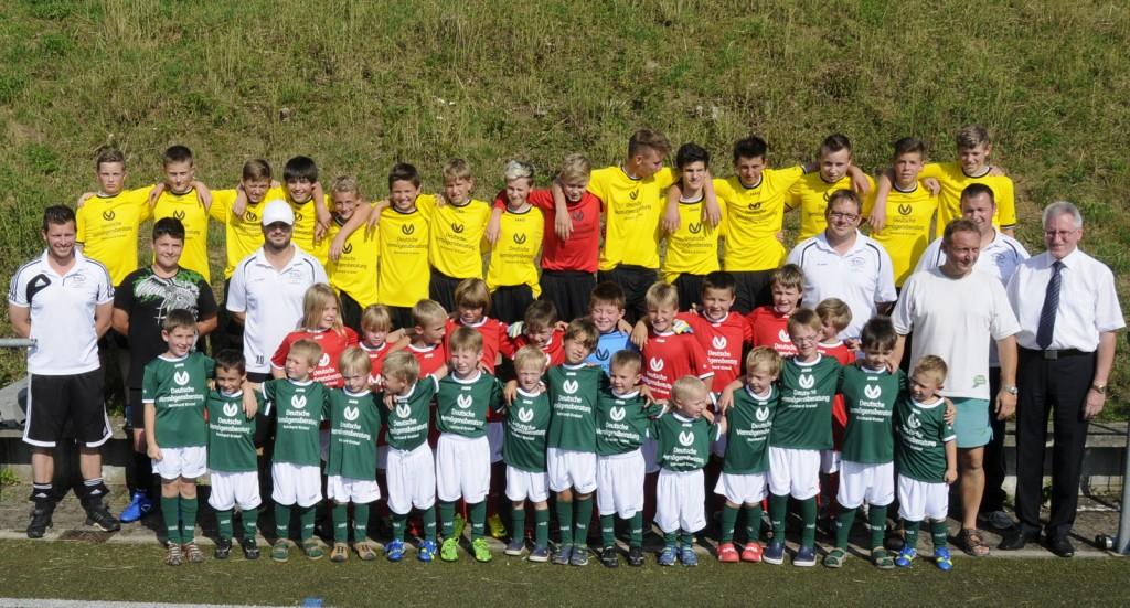 Vermögensberater Reinhard Kreisel übergibt die neuen Trikots an die Trainer und Spieler